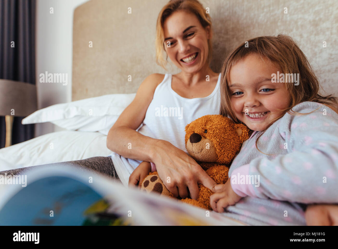 Happy mother and daughter looking at a book and smiling on bed. Pretty young woman reading a book to her daughter on bed. - Stock Image