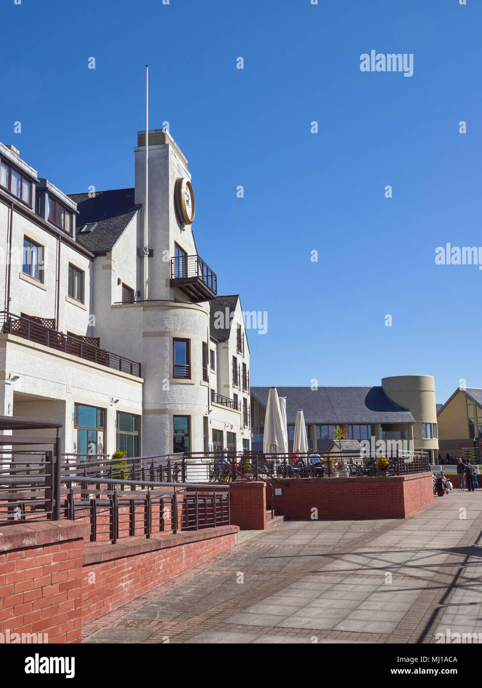 Looking up the terrace at the rear of the Carnoustie Golf Hotel at Carnoustie Golf Links, with Golfers sitting down enjoying a drink. Angus, Scotland. - Stock Image