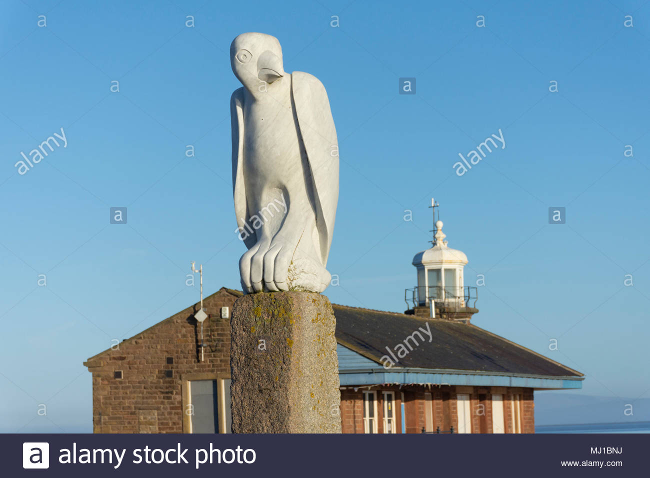A bird (sculpture) keeps a watchful eye near to the Stone Jetty in Morecambe, Lancashire, UK with the lighthouse in the background Stock Photo