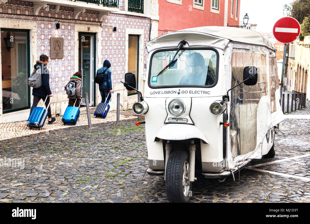 1 March 2018: Lisbon, Portugal - Electric tuk tuk in Lisbon's Old Town, with the slogan Love Lisbon Go Electric. - Stock Image