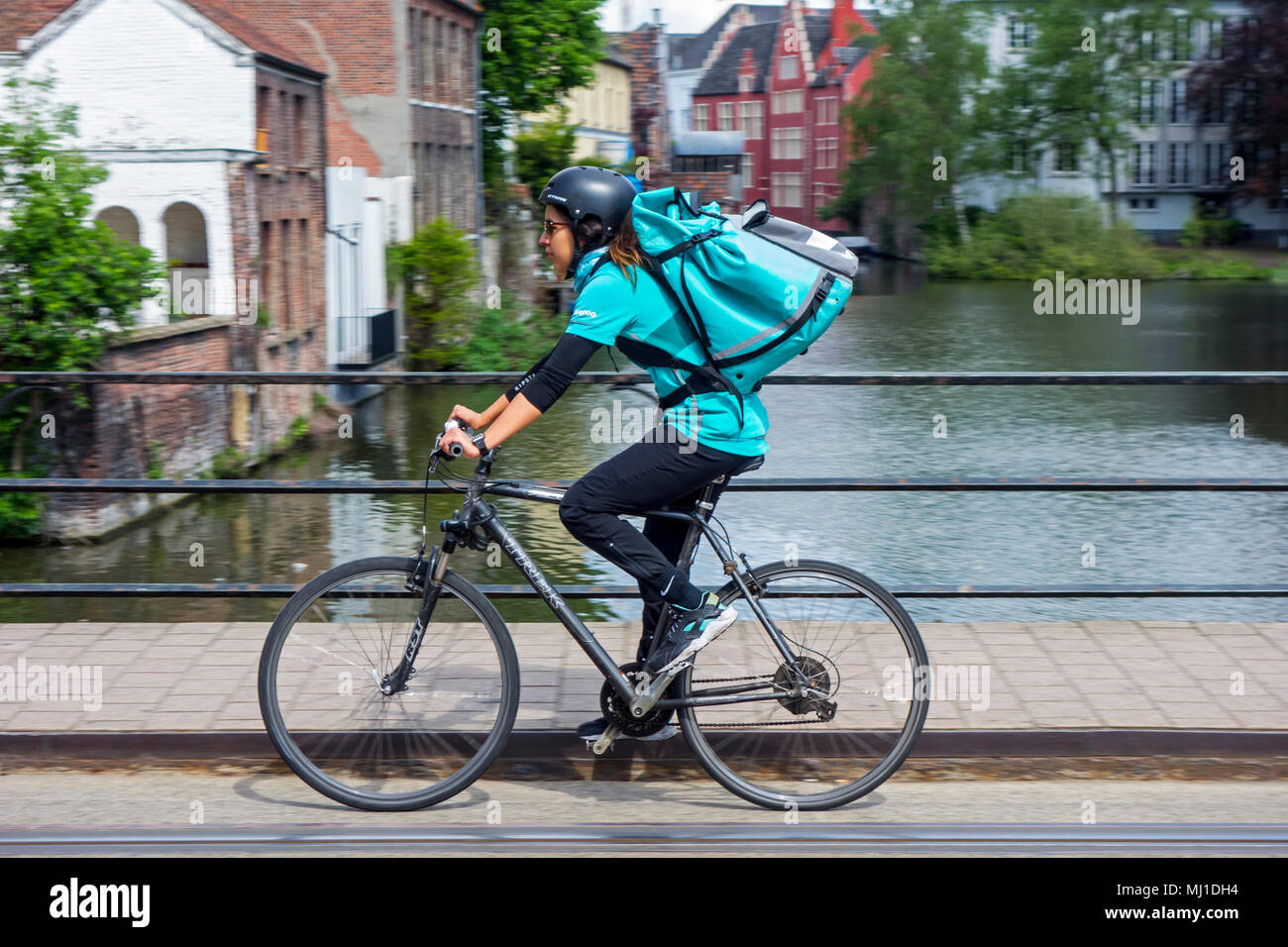 10bf42264fa Bicycle courier delivering meals in city center of Ghent, Belgium for  Deliveroo, British online