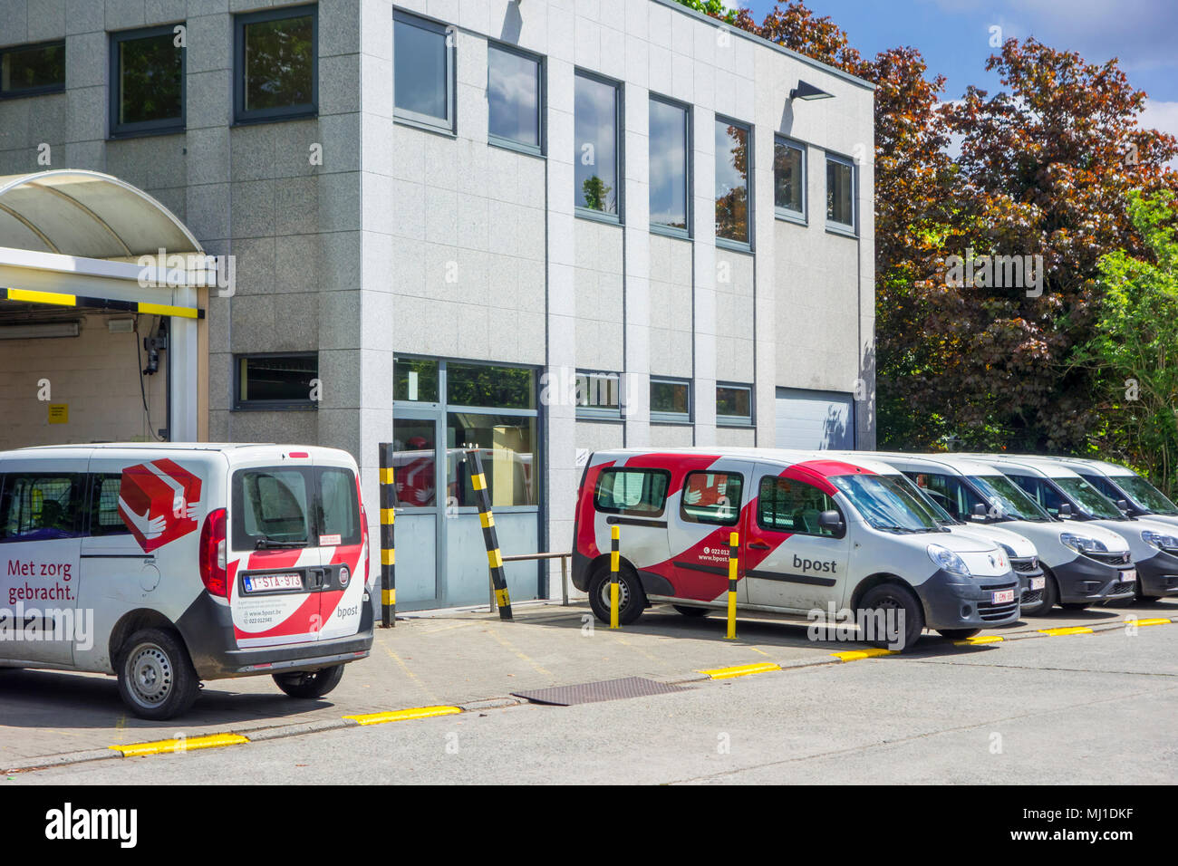 Red-white post delivery cars parked in front of a Bpost post office, Belgian company responsible for the delivery of national and international mail - Stock Image