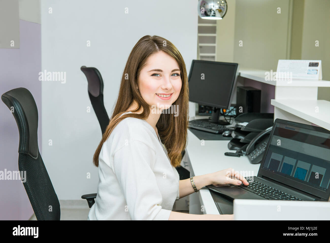 Portrait of skilled administrative manager working on laptop computer in office satisfied with occupation, young female receptionist organizing workin Stock Photo