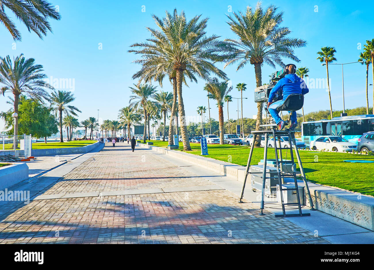 DOHA, QATAR - FEBRUARY 13, 2018: Cameraman conducts live TV broadcast from Corniche promenade in business Al Dafna district during the Day of Sport, o - Stock Image