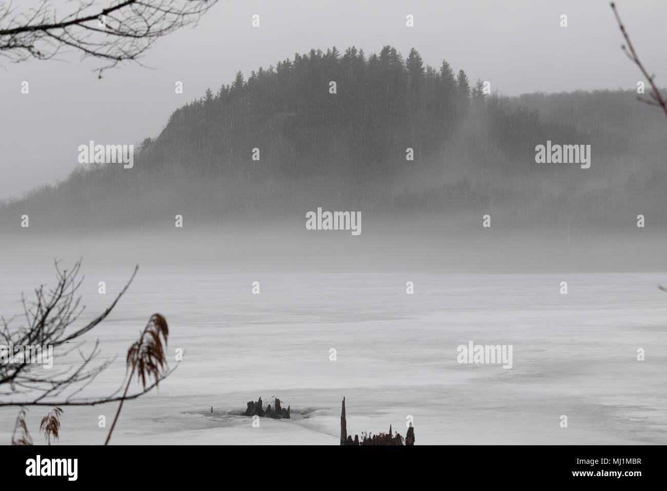 Paysage montagne de brume au printemps avec Lac enneigé - Stock Image