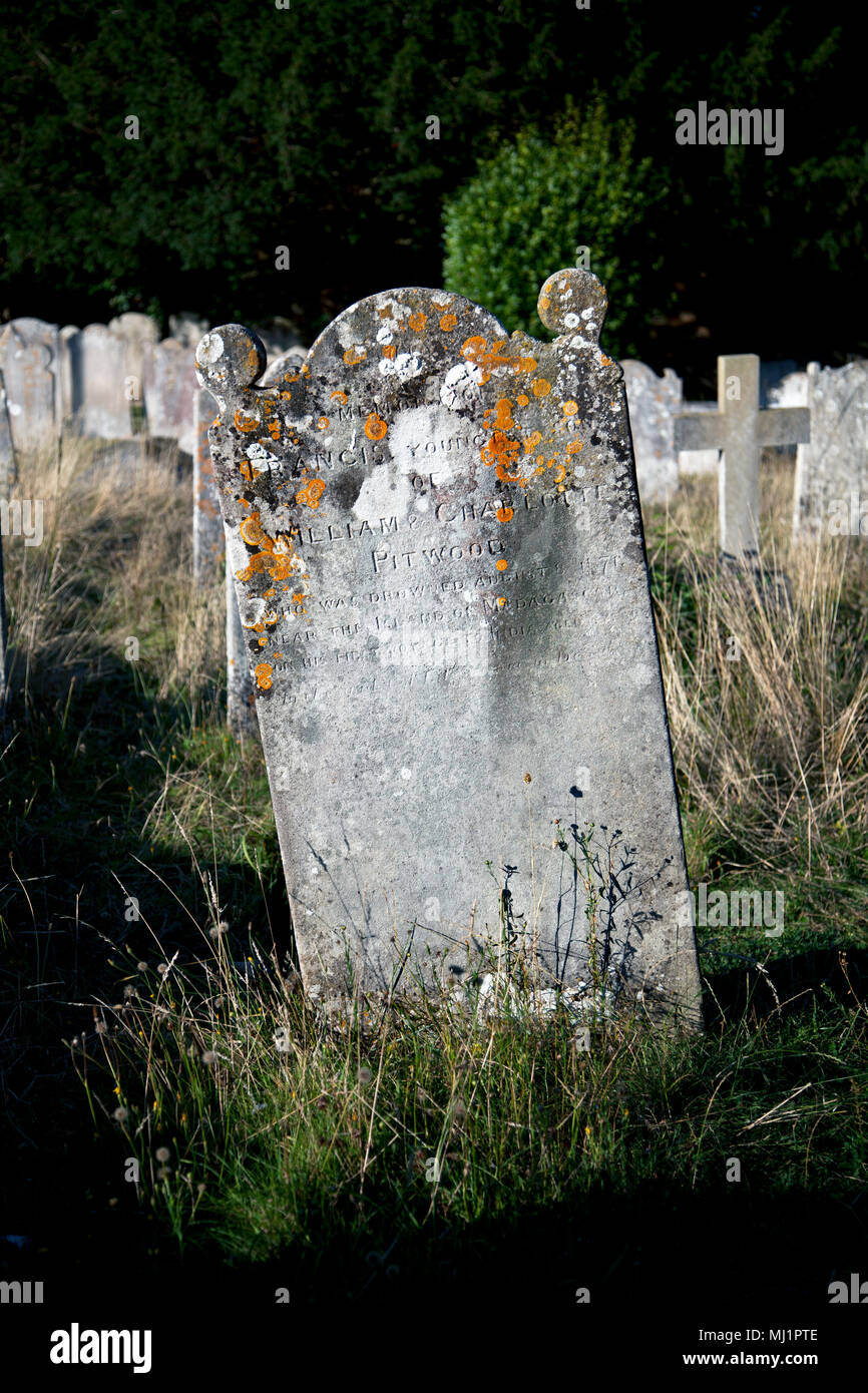 Made unreadable by three centuries of brutal seacoast weather, gravestones from another time flank St. Nicholas & St. Giles Parish Church in the hear - Stock Image