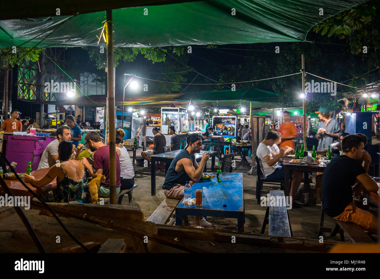 European turists and local residents sitting in the light of electrical bulbs at long tables having various streetfood in an indonesian nightmarket, a - Stock Image