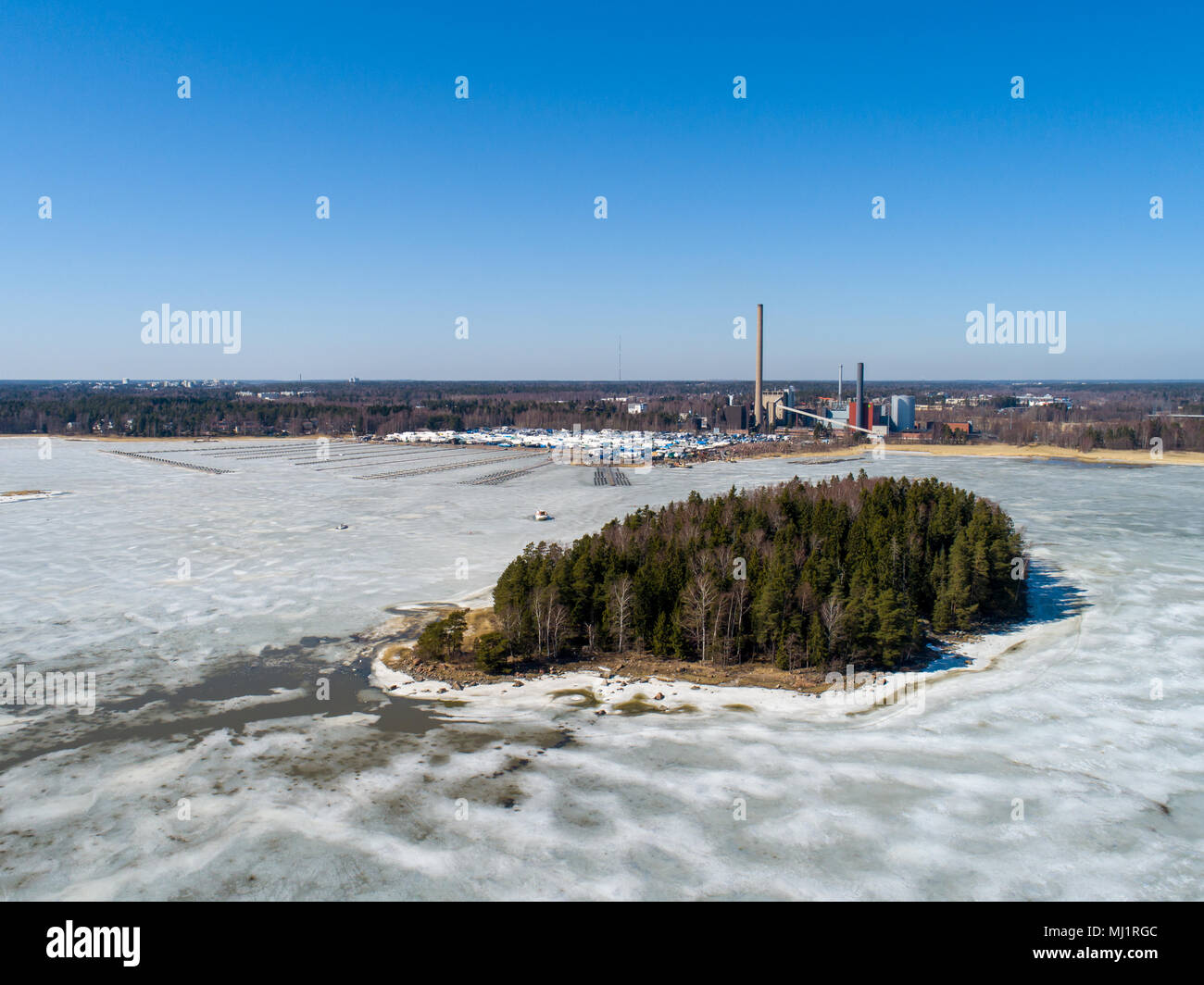 Finland Espoo, Suomenoja Marina With The Boats Still On Land At Winter  Storage, Power Plant In The Back And Small Island Of Pirisaari In The  Foregroun