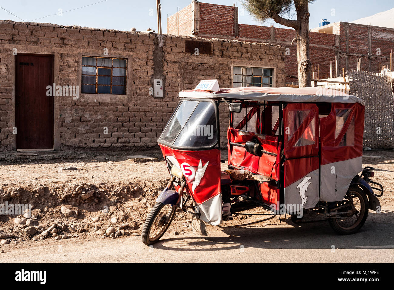 Moto taxi parked in front an adobe house. Acari, Department of Arequipa, Peru. - Stock Image