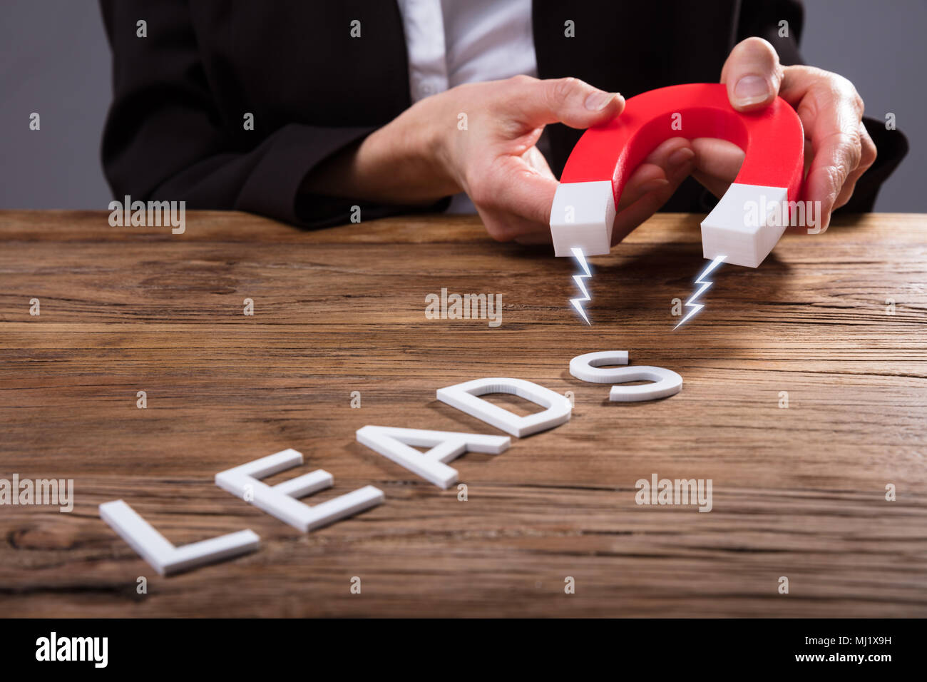Businessperson Attracting White Lead Text With Horseshoe Magnet Over Wooden Desk Stock Photo