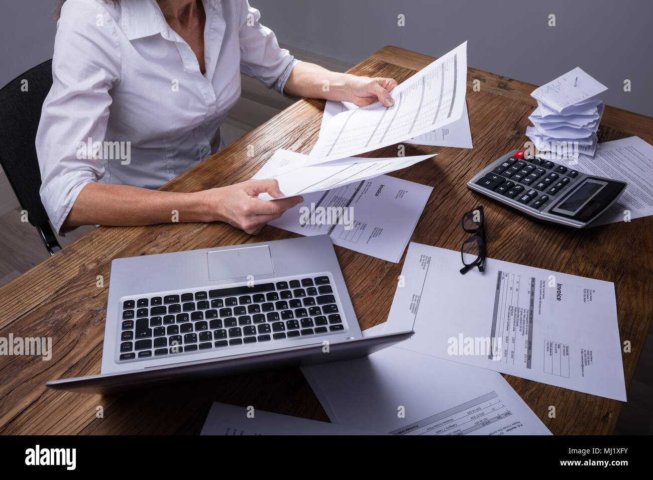 Elevated View Of Businessperson's Hand Holding Documents Over Wooden Desk - Stock Image