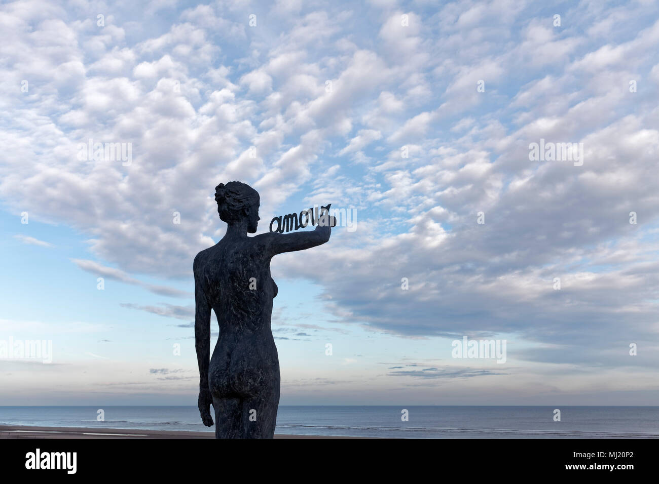 Woman writes French word Amour, Love, in the sky, bronze sculpture by Belgian sculptor Linde Ergo, De Haan, North Sea - Stock Image