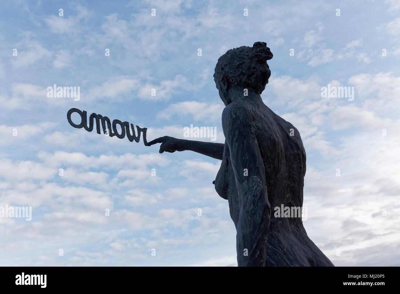 Woman writes French word Amour, Love, in the sky, bronze sculpture by Belgian sculptor Linde Ergo, De Haan, West-Flanders - Stock Image