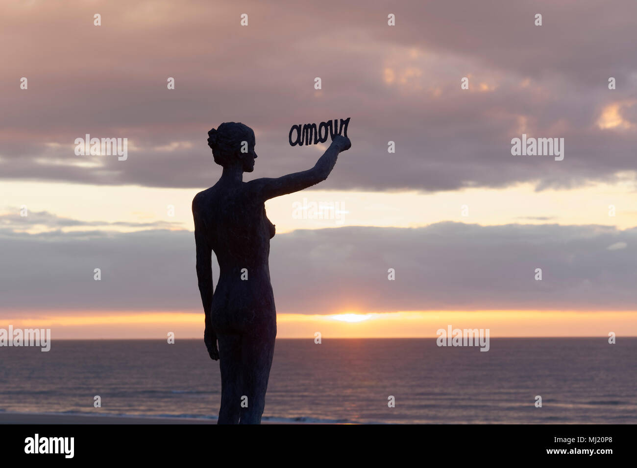 Woman writes French word Amour, Love, in the sky at sunset, bronze sculpture by Belgian sculptor Linde Ergo, De Haan, North Sea - Stock Image