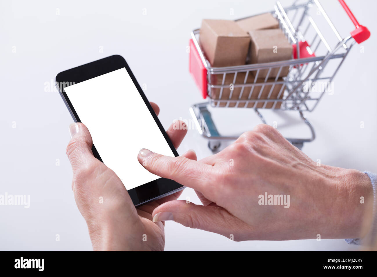 A Person Hand Showing Mobile Phone With Blank Screen And Shopping Cart On The Background - Stock Image