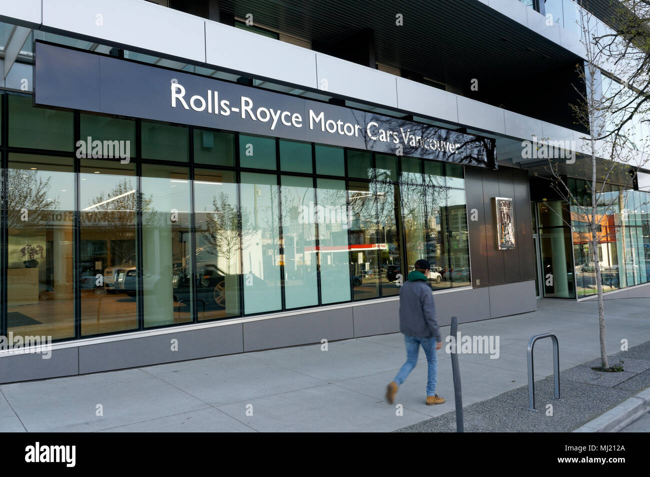 Man walking past a Rolls Royce Motor Cars dealership in Vancouver, BC, Canada - Stock Image