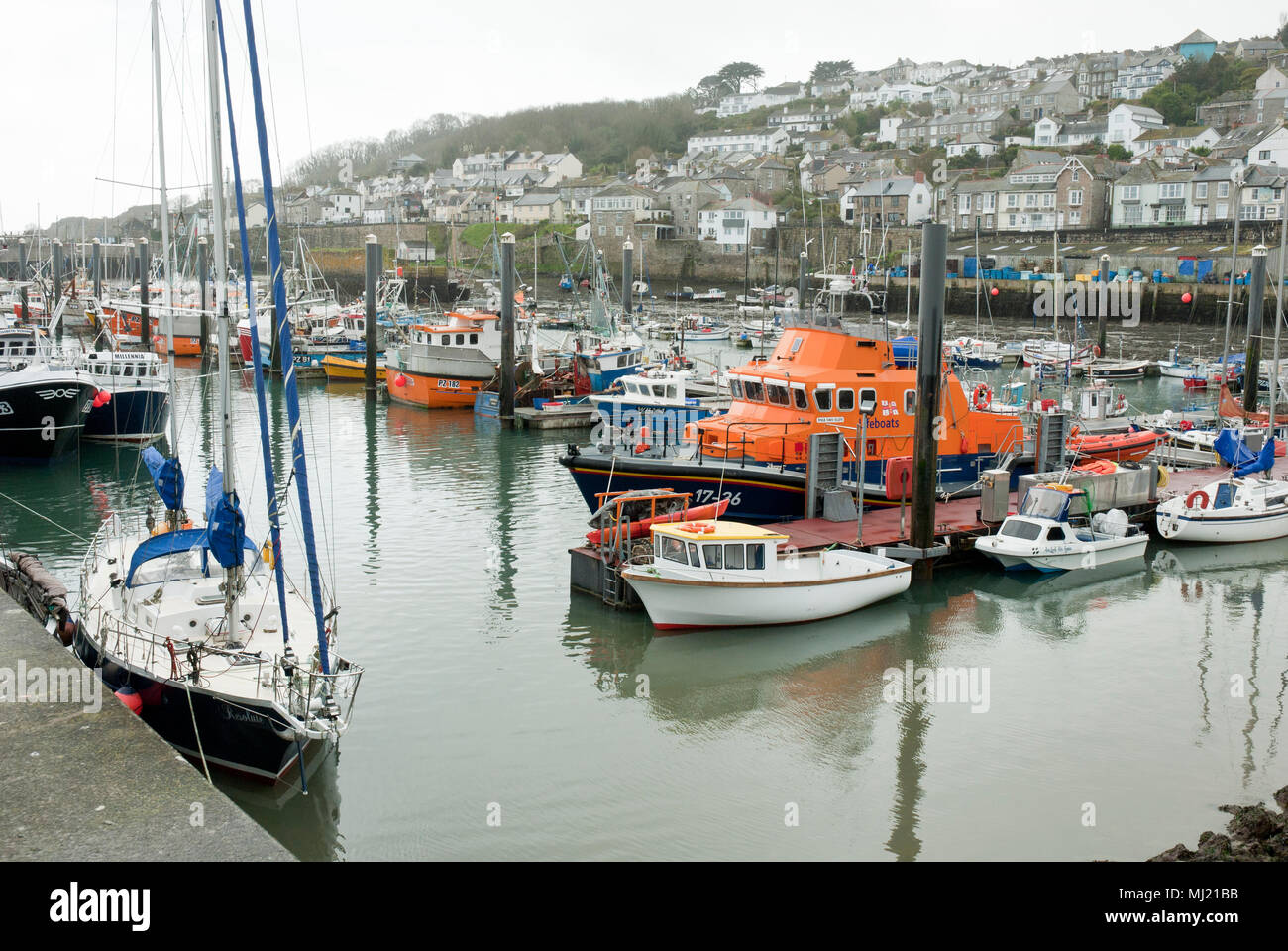 A variety of fishing, boats, yachts and pleasure craft moored in Newlyn Harbour with the town of newlyn in the background. Stock Photo