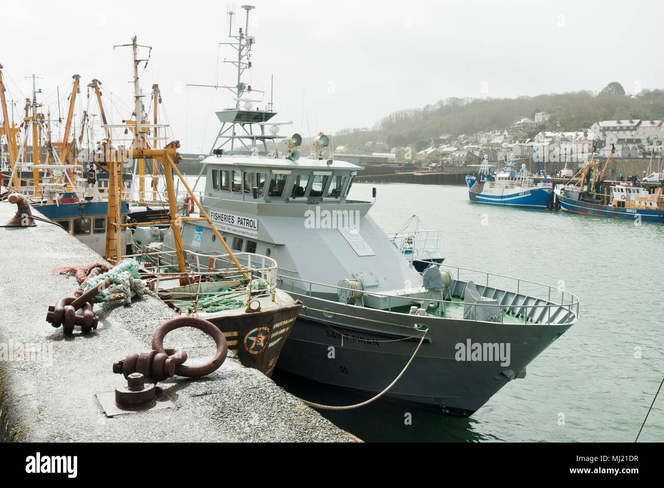 The Fisheries Patrol vessel, Saint Piran, in the foreground with fishing boats and the town of Newlyn in the background. - Stock Image
