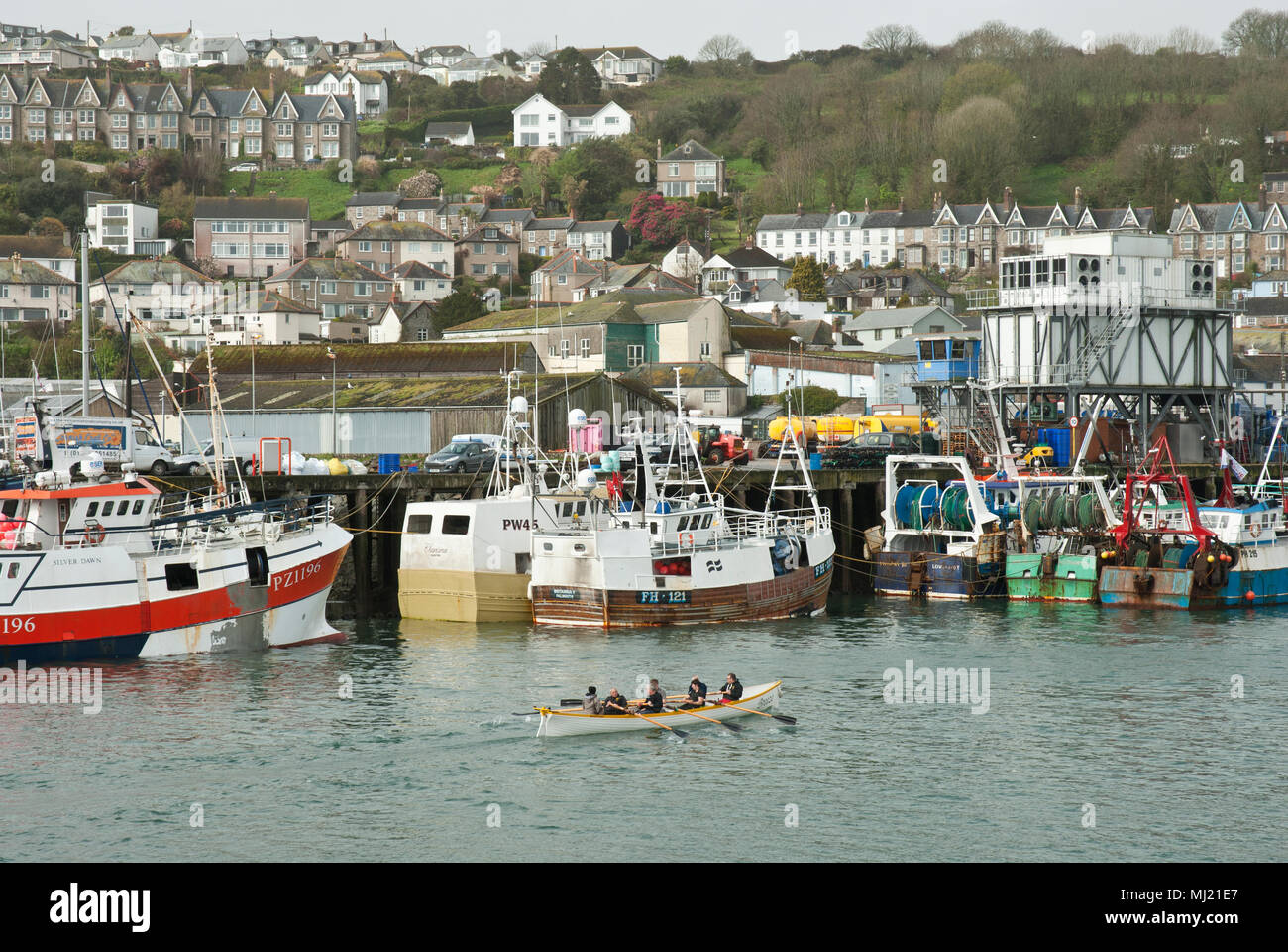 The traditional Cornish racing gig Pendeen training in Newlyn Harbour in the foreground with fishing vessels and the town of Newlyn in the background. - Stock Image
