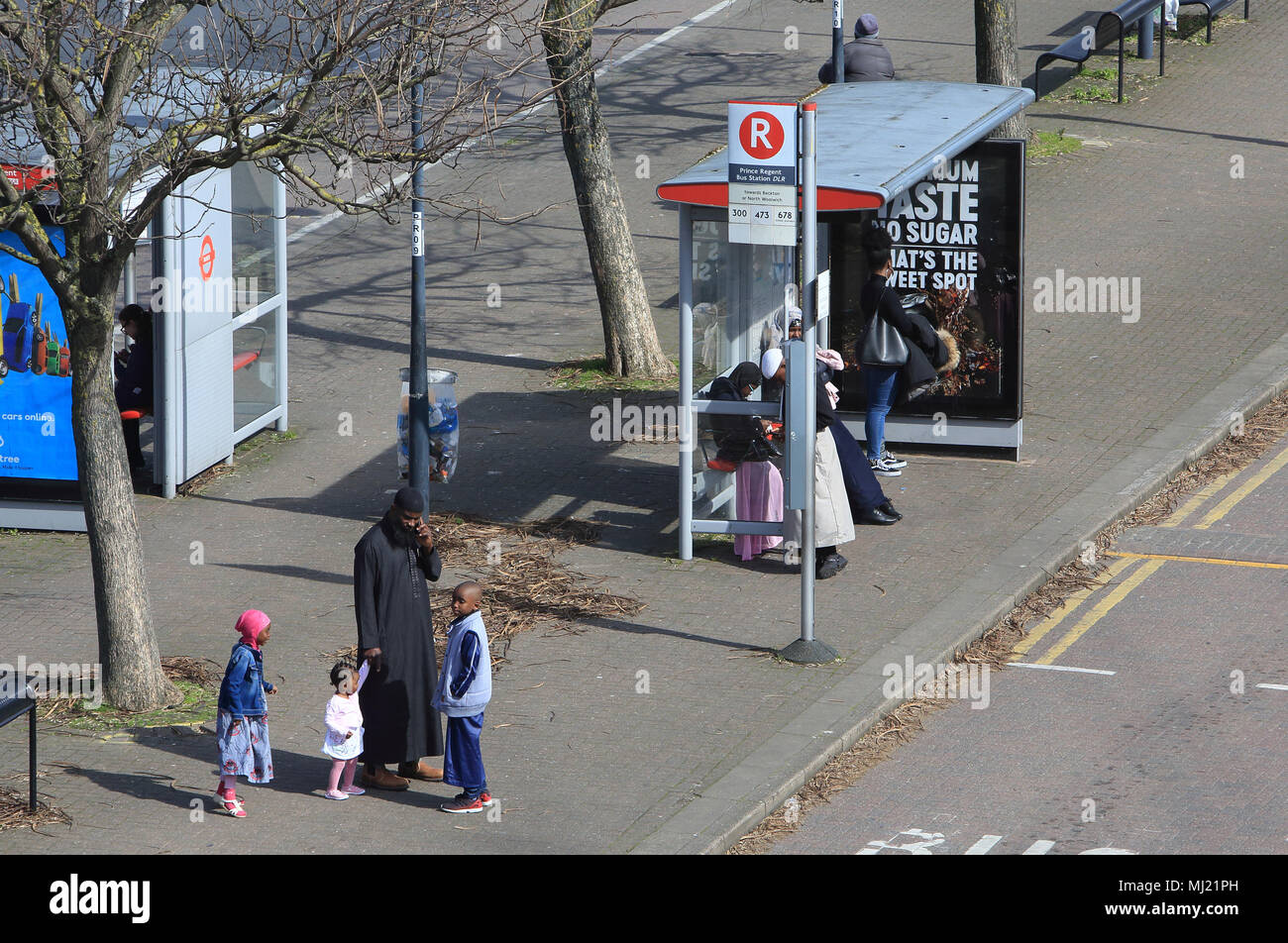 People waiting at the bus stop in diverse and multicultural Canning Town, in east London, England, UK - Stock Image