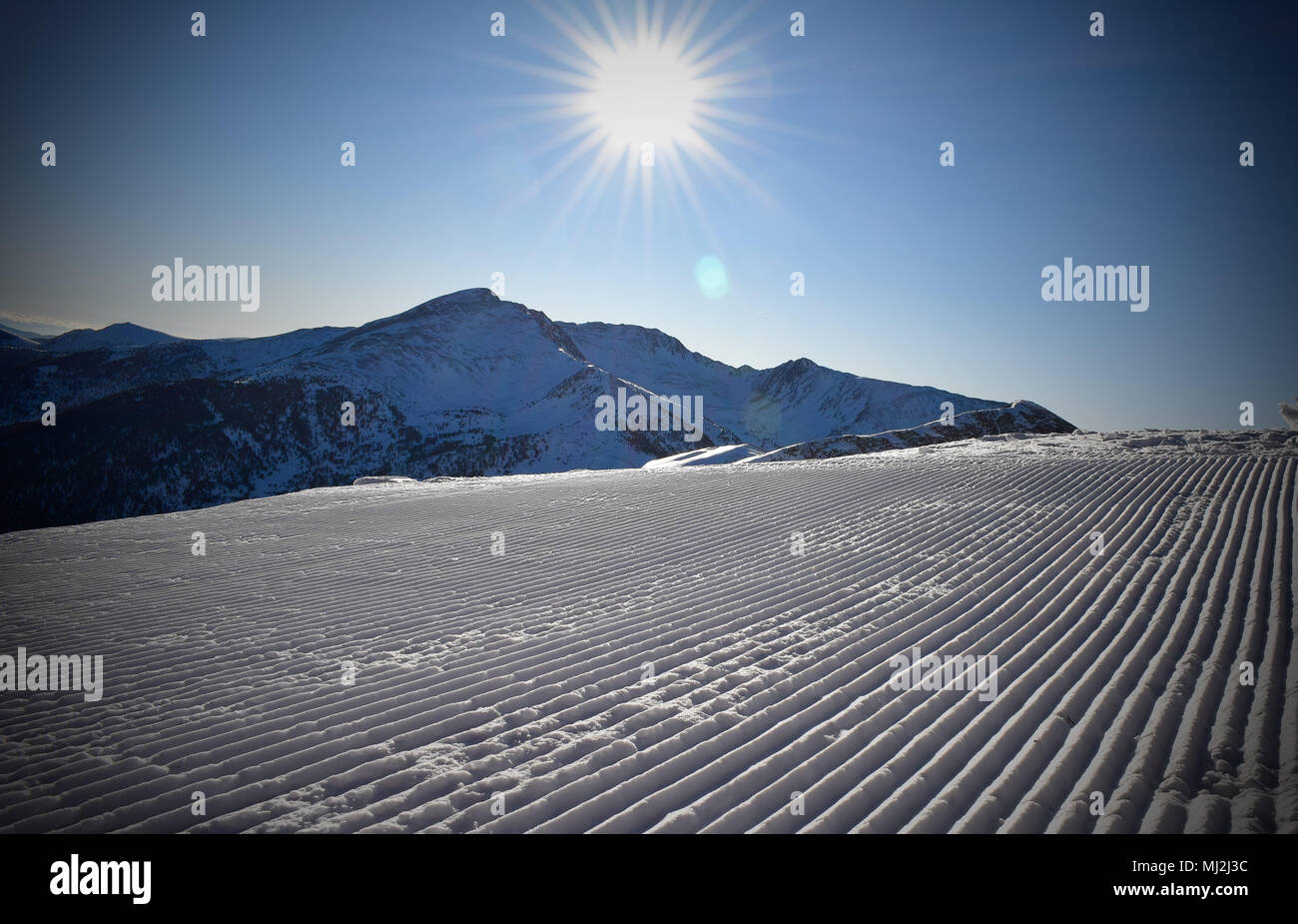Sunny piste in ski resort - Stock Image
