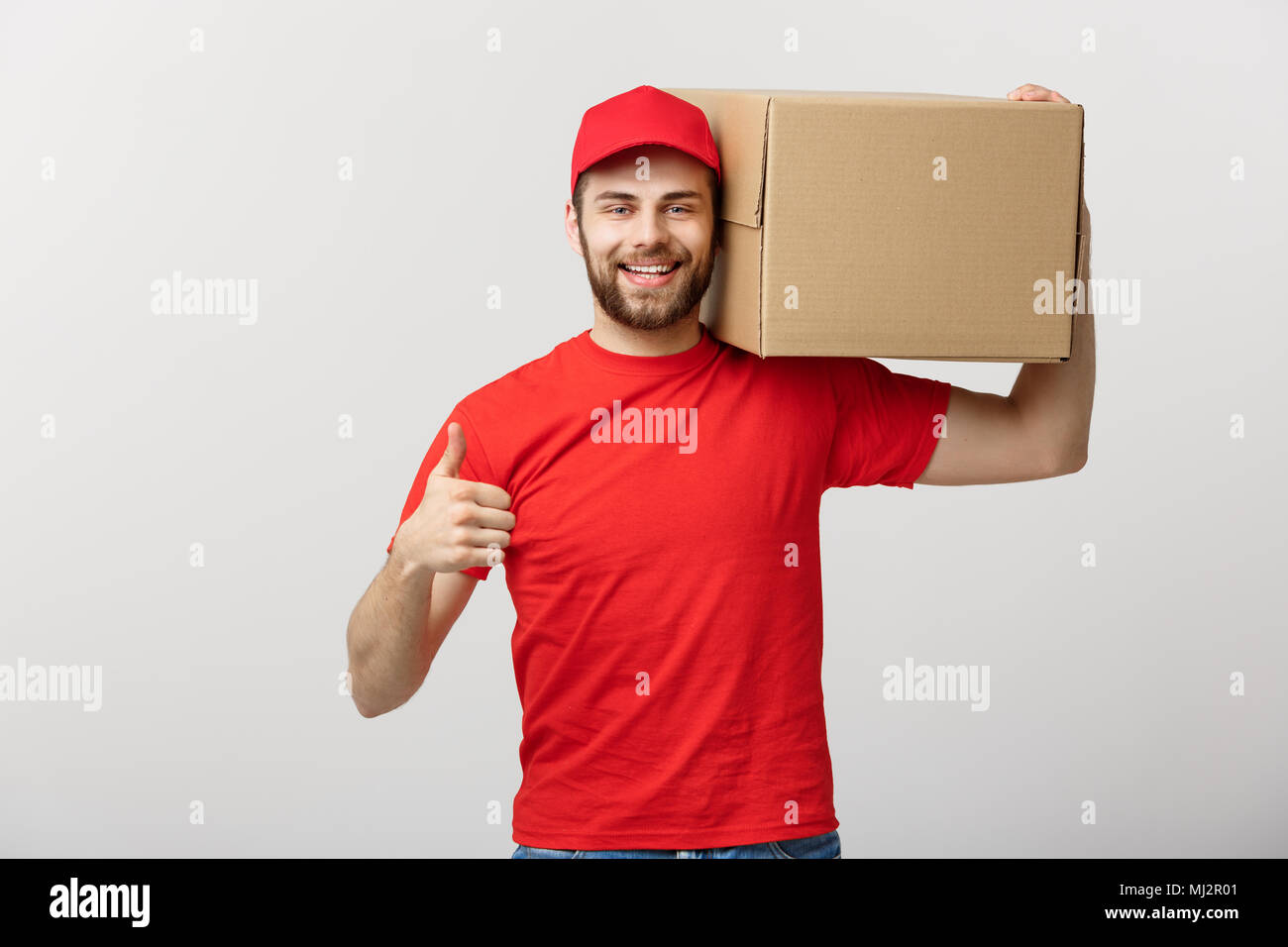Cheerful young handsome delivery man holding a cardboard box and showing his thumb up while standing against grey background - Stock Image