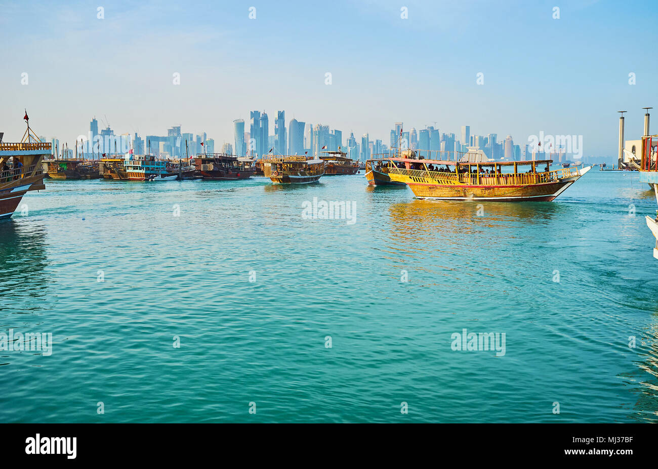 DOHA, QATAR - FEBRUARY 13, 2018: The numerous old wooden dhows are moored in harbor, this tourist fleet attracts people to enjoy sea trips, on Februar - Stock Image