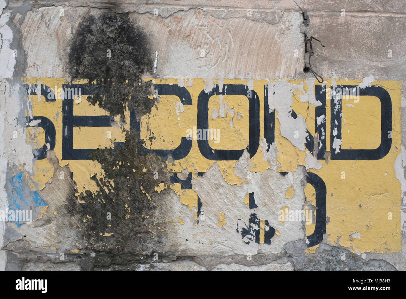 the old peeled inscription second hand on a brick wall - Stock Image