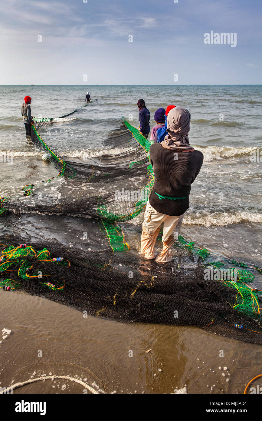 Men from the local fishing village lay out and haul in their near mile-long seine net at Baybay Beach, Roxas City, Capiz, Panay, Philippines. - Stock Image