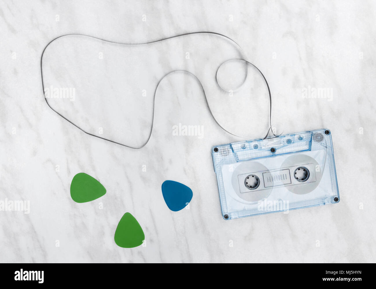 Blue audio tape and guitar picks on marble background. - Stock Image
