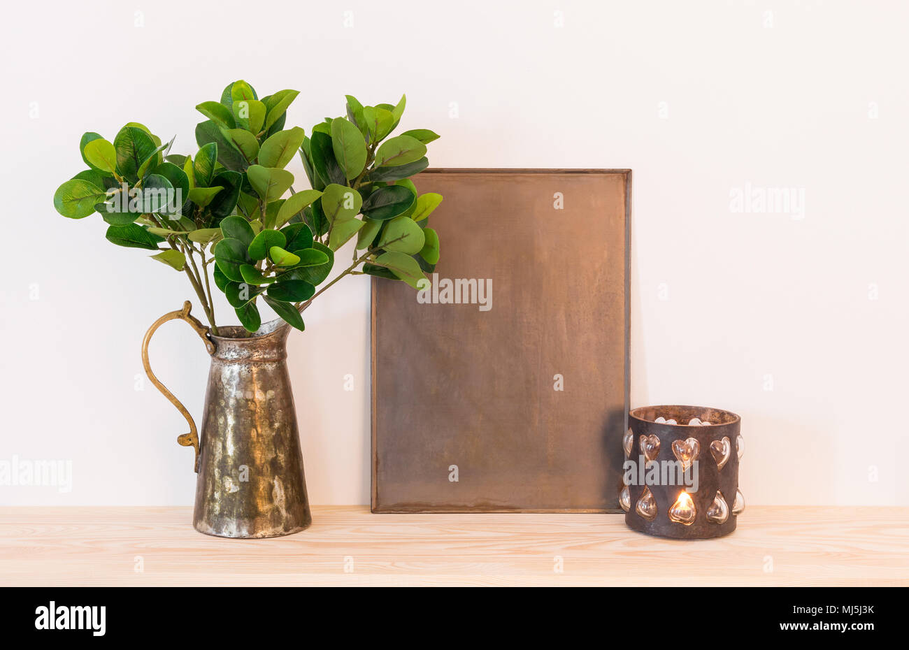 Vintage style home decor composition. Metal frame with copy space, ficus in antique jar and candle. Stock Photo