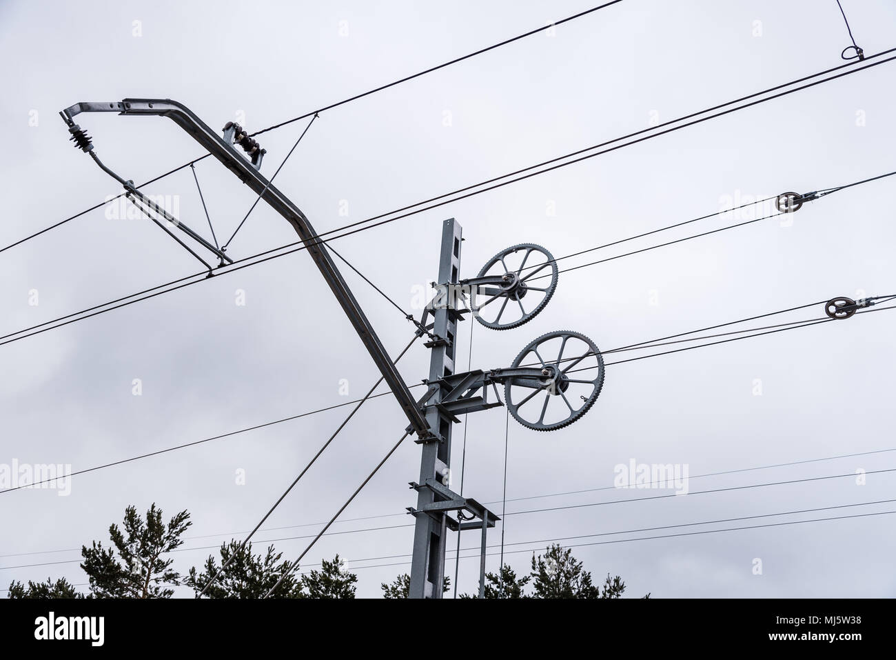 Catenary wires for power supply to railway against sky. Stock Photo