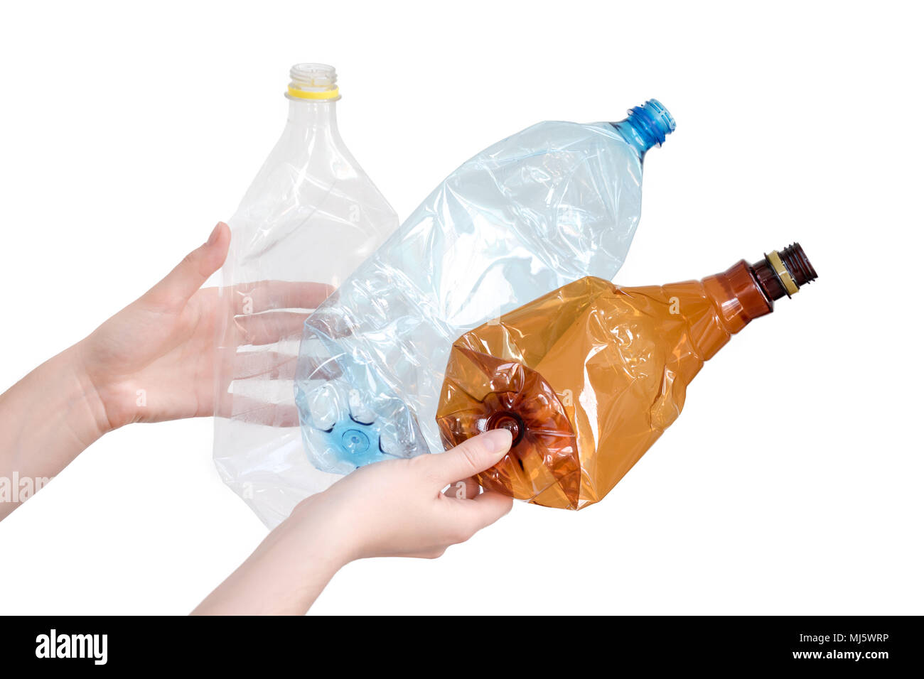 Female hands holding different types of crushed plastic bottles isolated on white. Recyclable waste. Recycling, reuse, garbage disposal, resources, environment and ecology concept - Stock Image