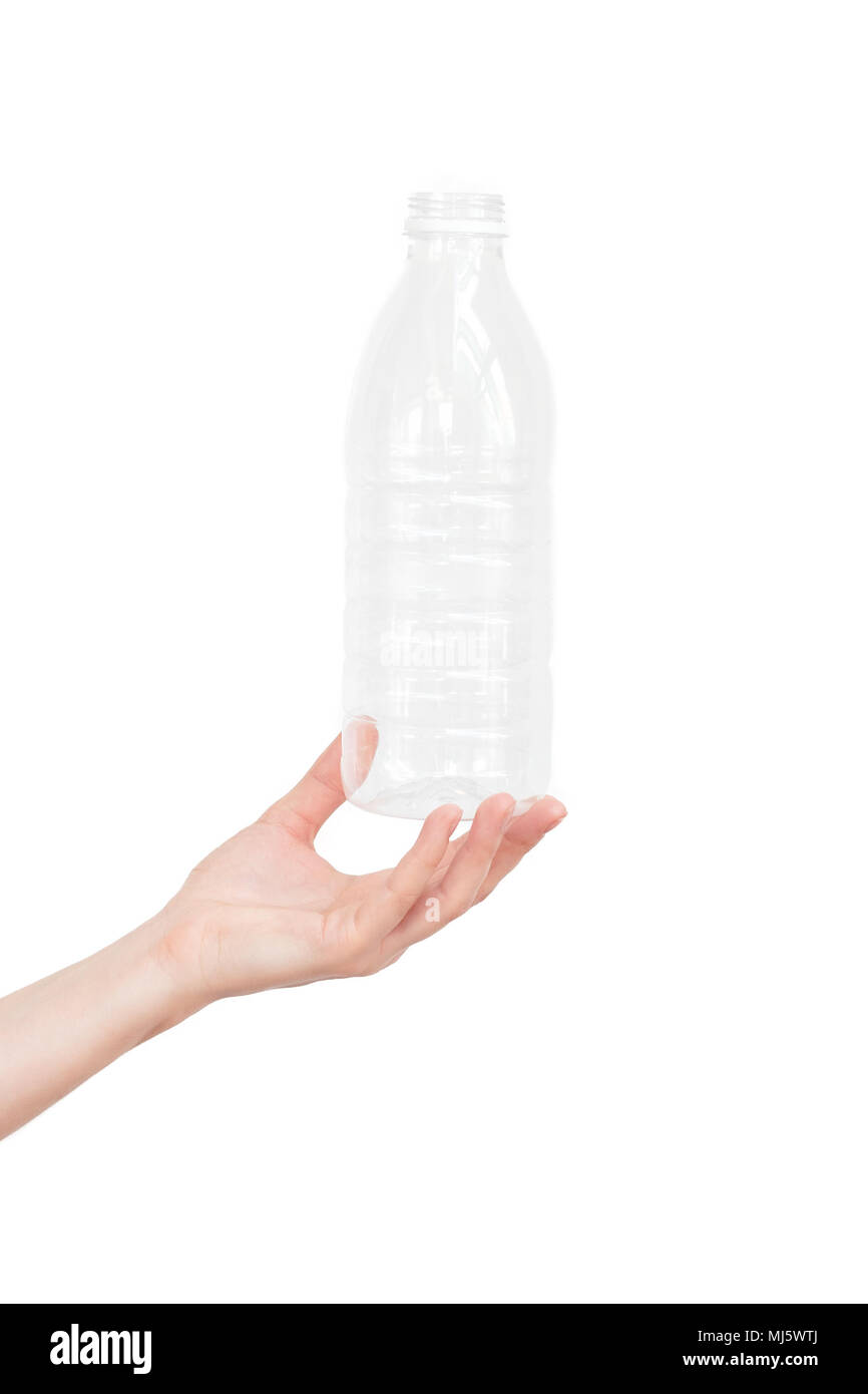 Female hand holding empty plastic bottle isolated on white. Recyclable waste. Recycling, reuse, garbage disposal, resources, environment and ecology concept - Stock Image