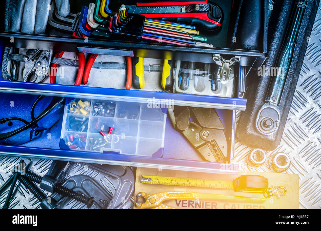 Top view of tools in box on checkered plate background in workshop. Service tools set. Home building and electrical tools. Plumber hand tools. Technic - Stock Image