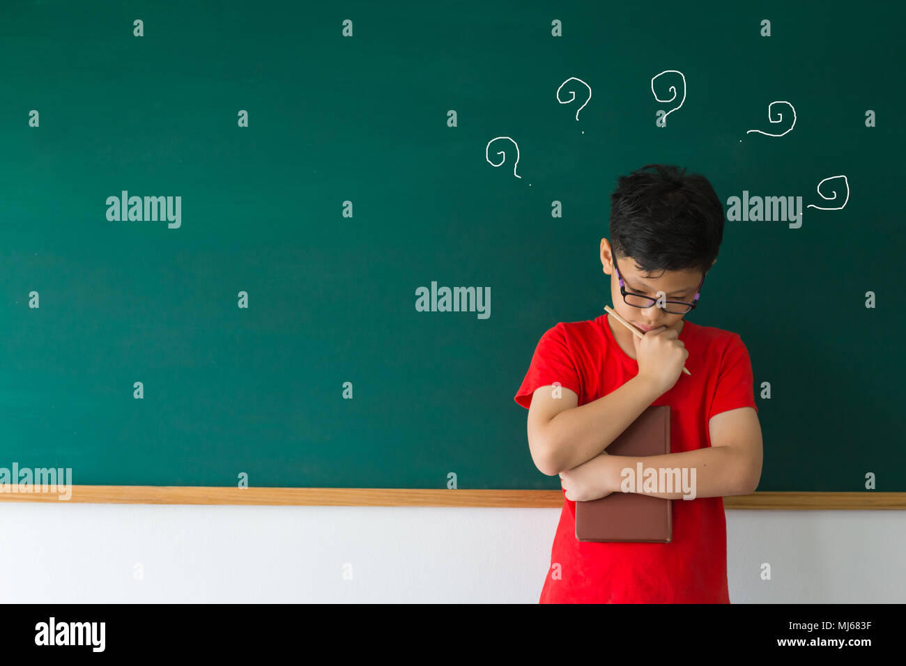 Smart boy in red t-shirt with thinking near chalkboard