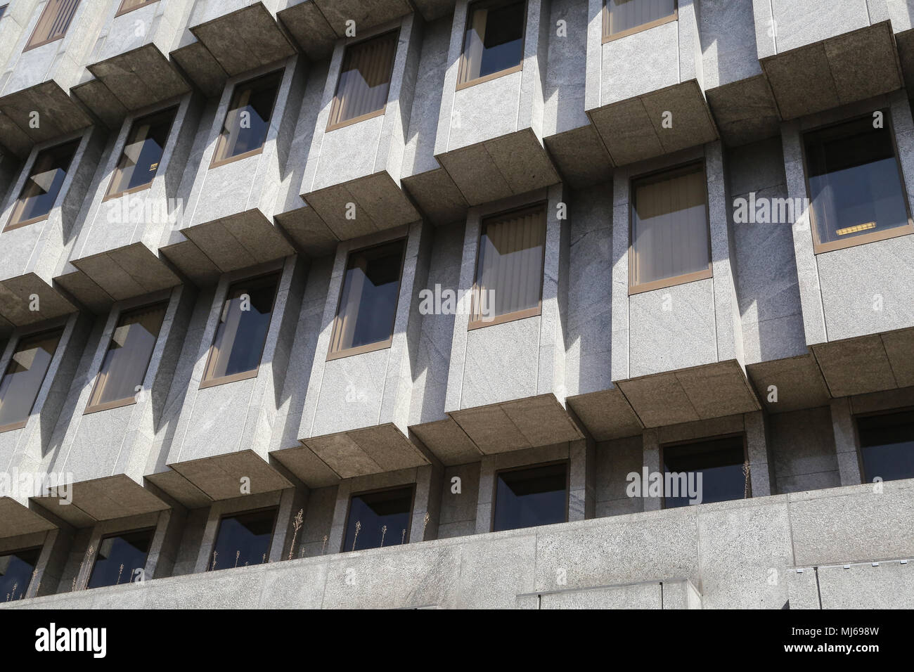 Section of a modern building in Leeds City Centre West Yorkshire. The architect designed a repeating pattern of glass and concrete of​ geometric lines - Stock Image