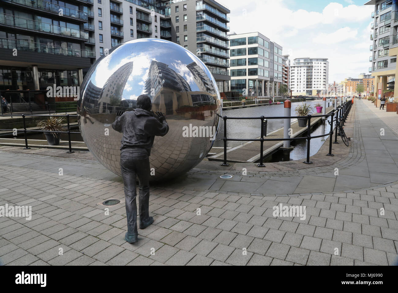 A Reflective Approach is a two-part sculpture consisting of 2 life-size bronze figures pushing two reflective stainless steel spheres towards a canal. - Stock Image