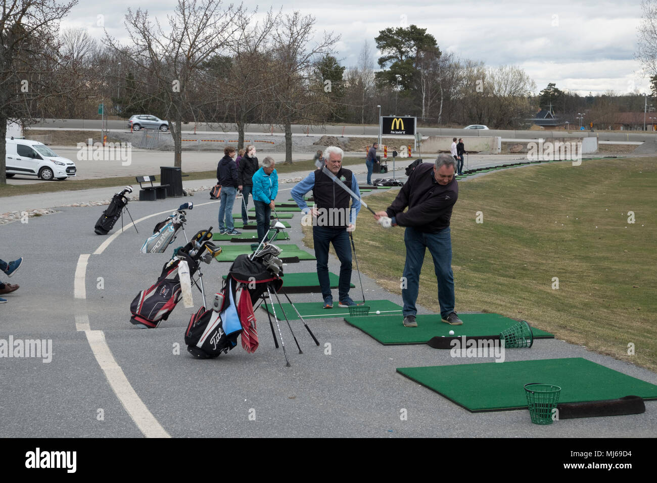 People train on the driving range in front of the golf course, Sollentuna, Sweden. - Stock Image