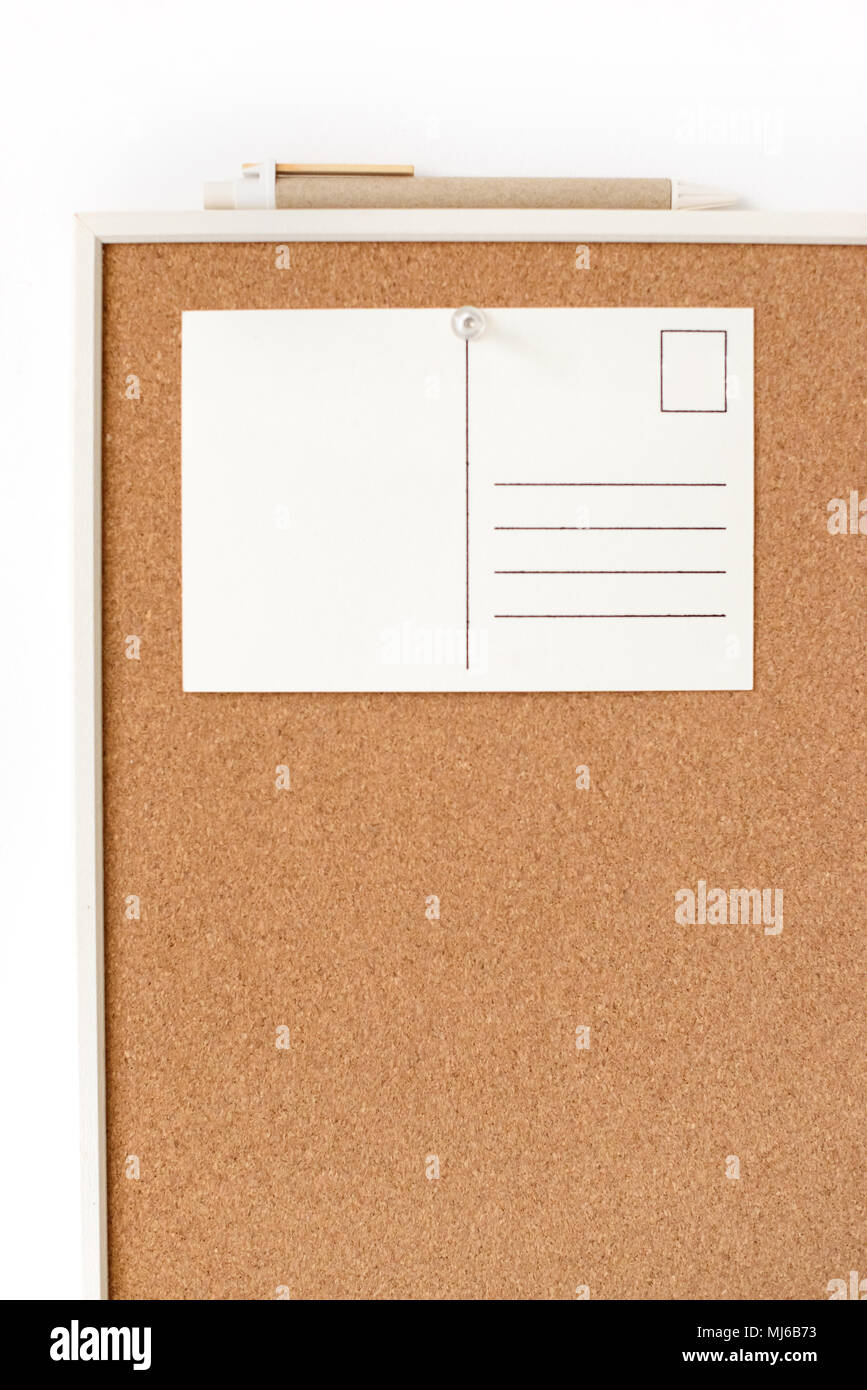 White Postcard With Free Copy Space Pinned On Cork Board On A Wall. Office  Or School Concept.
