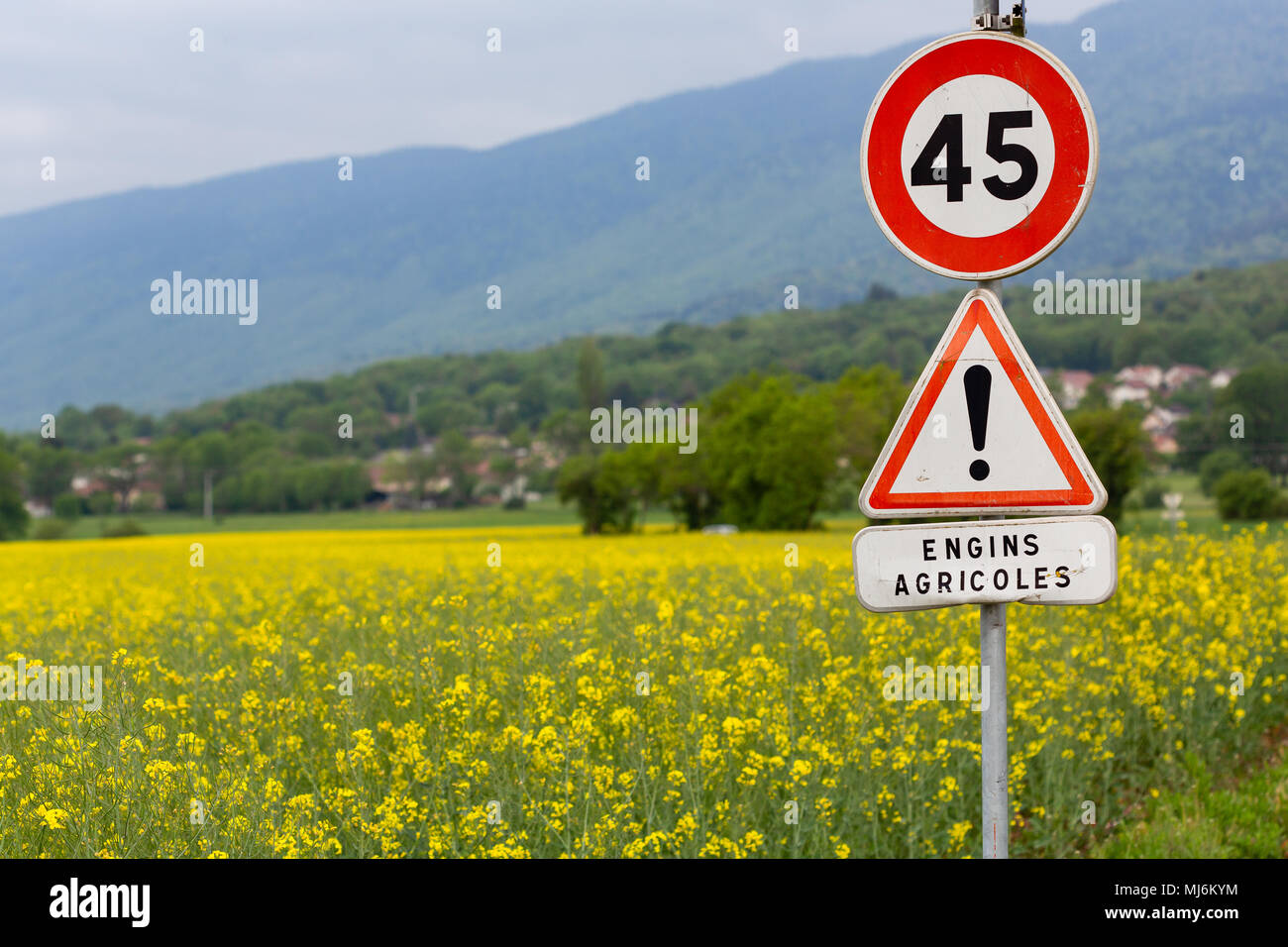 A round and triangular road sign announcing a speed restriction for agricultural vehicles. - Stock Image