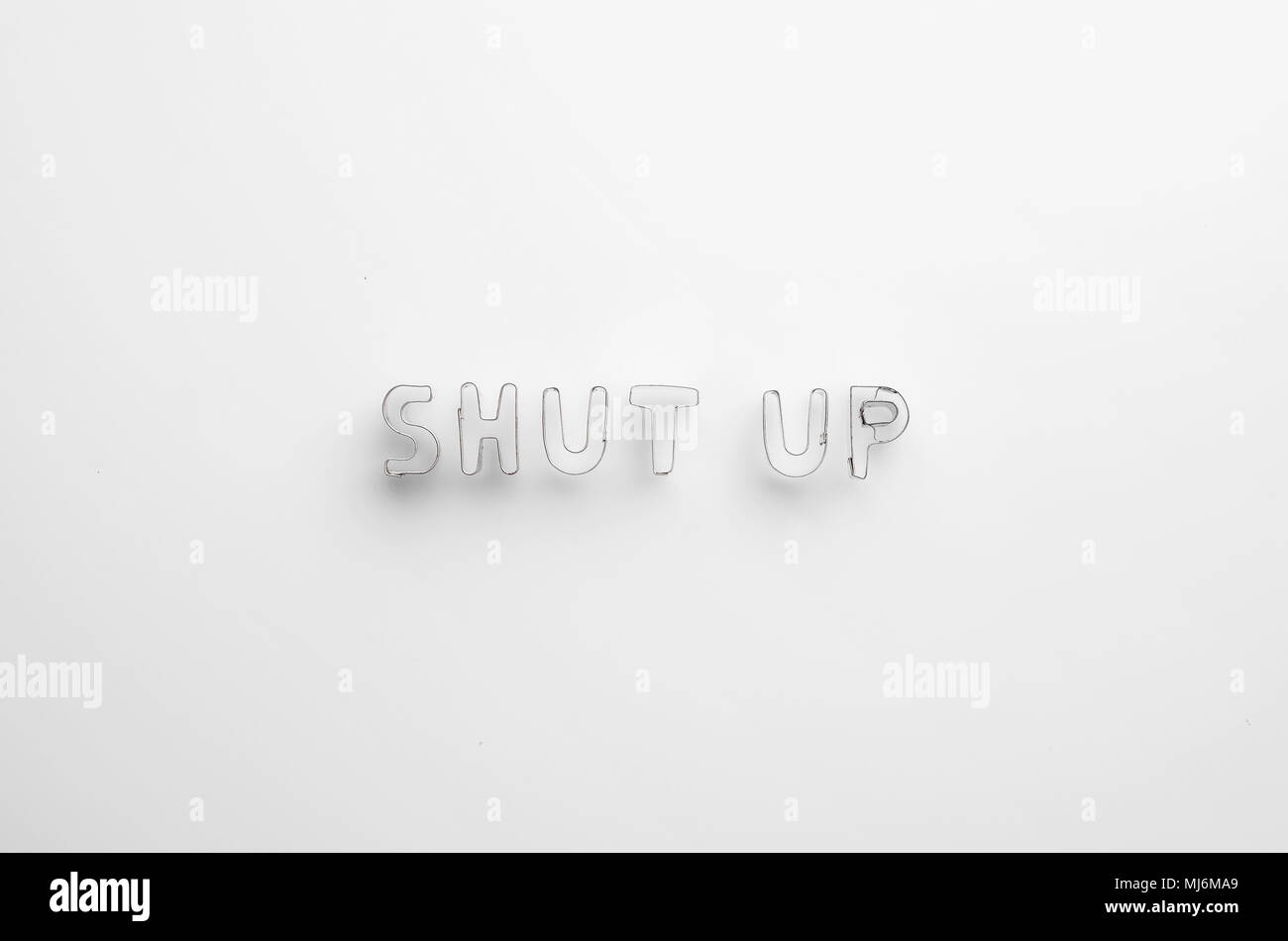 Shut up word over white background, top view - Stock Image