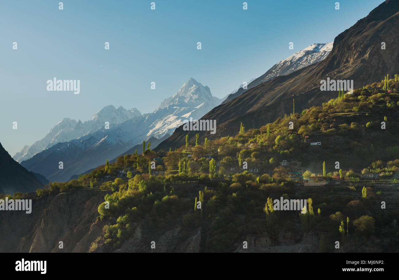 Countryside landscape, Snow mountain peak and rural village with forest on cliff at Hunza valley in Pakistan - Stock Image
