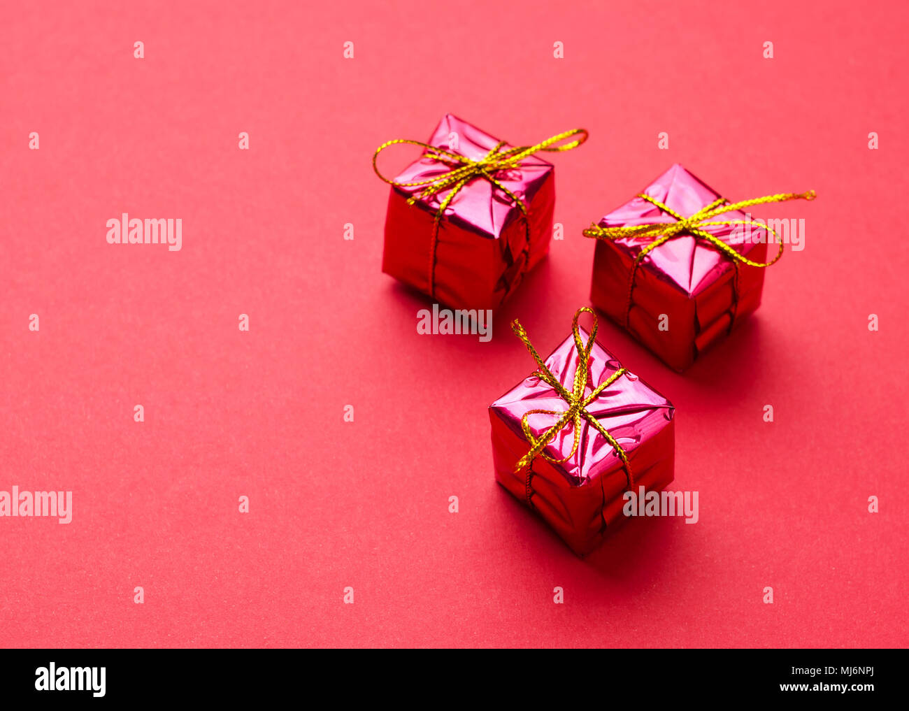 Small Red Christmas Gift Boxes over red background with space for ...