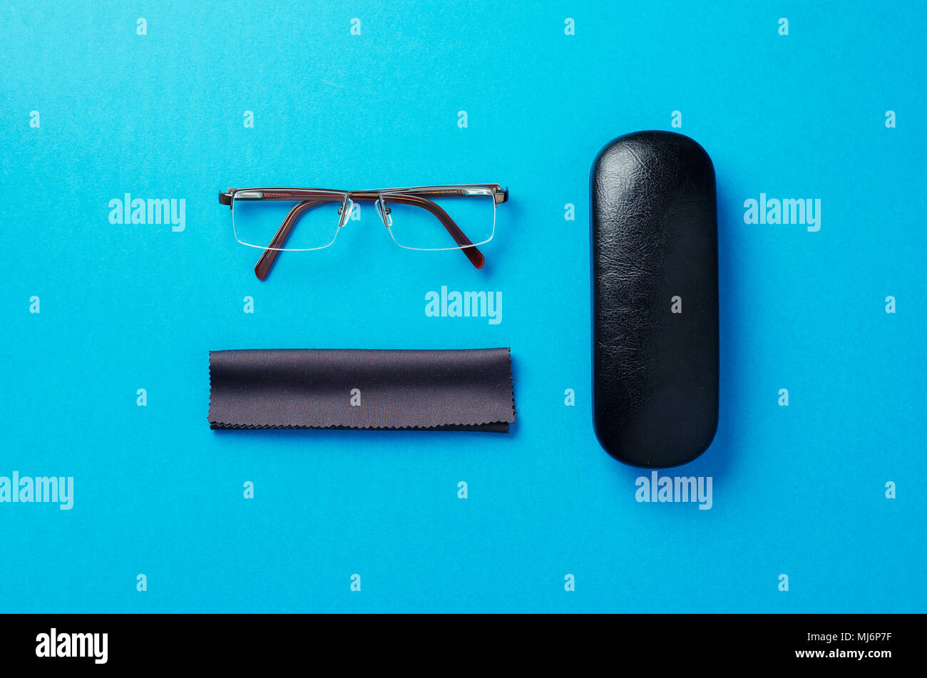 Eye glasses, case and fabric organized over blue background, above view. - Stock Image