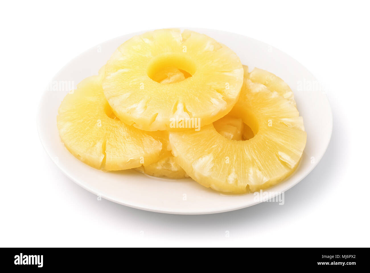 Canned pineapple slices on plate isolated on white - Stock Image
