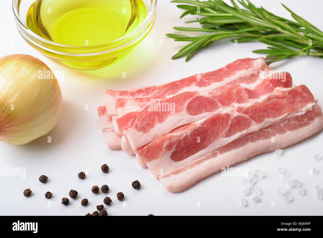 Raw bacon slices with condiments on white background - Stock Image