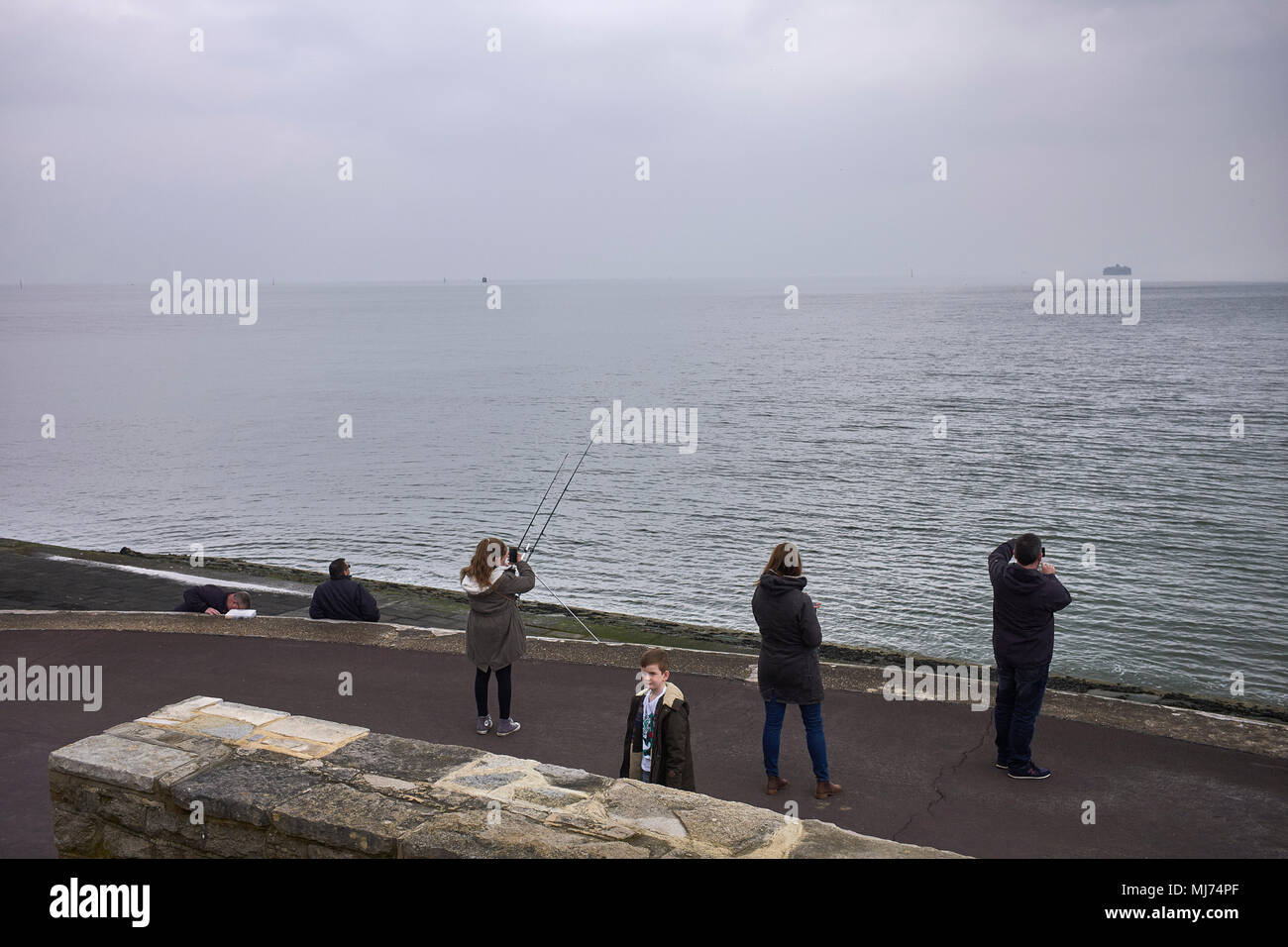 A family stop to take phone pics out to sea while a boy looks towards camera at Southsea, Hampshire - Stock Image