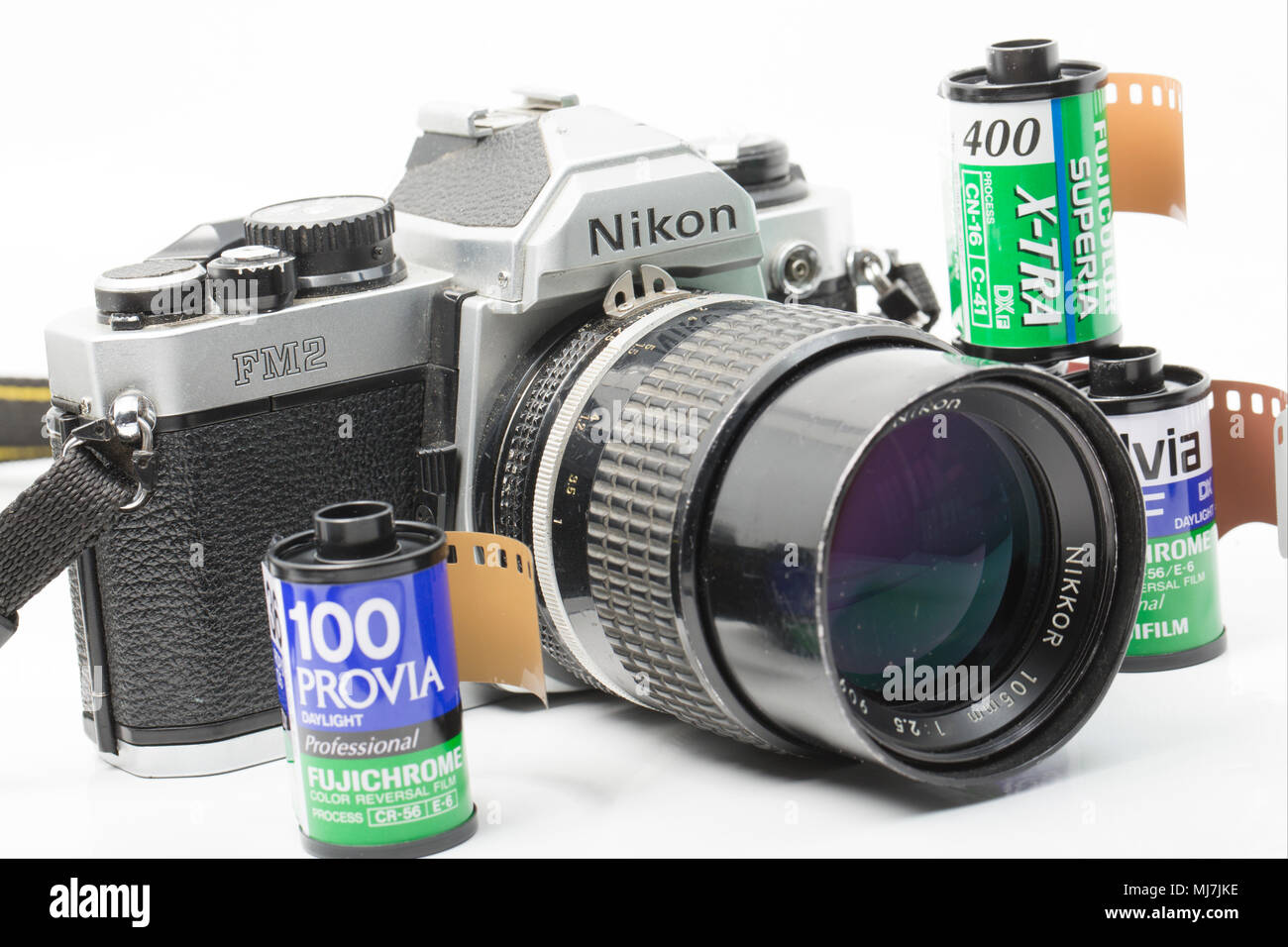 A Nikon FM2 film camera bought in the early 1990s fitted with a Nikkor 105mm 2.5 lens. Dorset England UK. It is pictured with some rolls of Fuji Film. - Stock Image