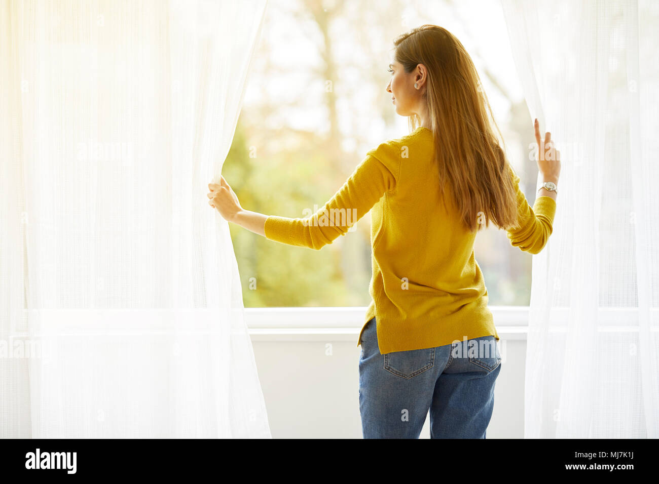 Attractive woman opening curtains - Stock Image
